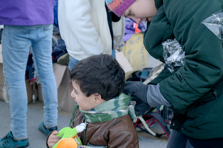 A social worker from Iliaktida helps a child put his scarf on.