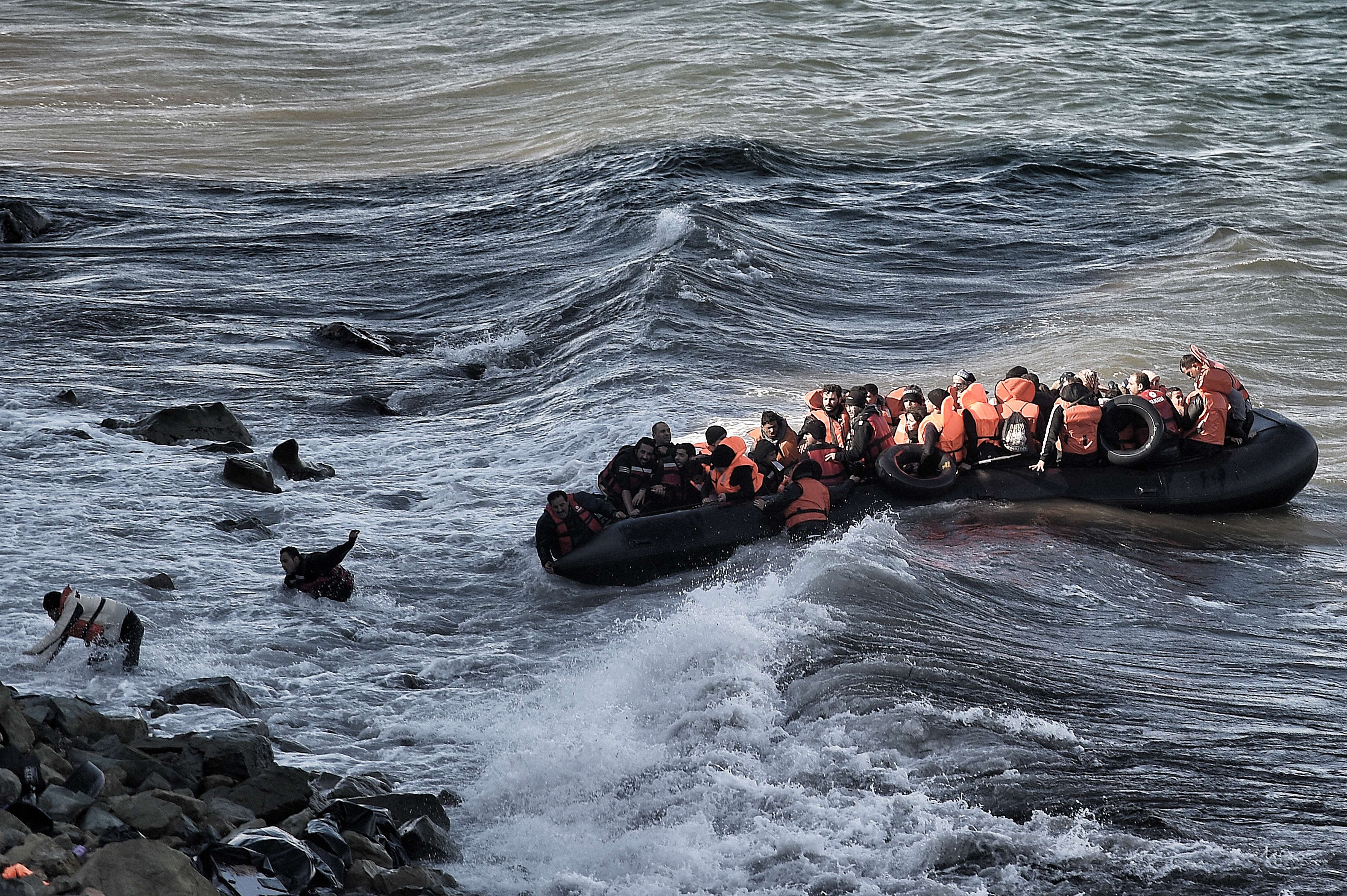 Refugees and migrants try to reach the shore on the Greek island of Lesvos, despite a rough sea, on October 30, 2015, after crossing the Aegean sea from Turkey. Photo credit: ARIS MESSINIS/AFP/Getty Images